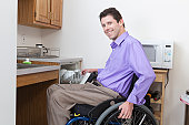 Man in wheelchair with spinal cord injury putting dishes in an accessible dishwasher