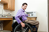 Man in wheelchair with spinal cord injury removing cup from an accessible microwave