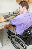 Man in wheelchair with spinal cord injury washing glass in an accessible kitchen sink
