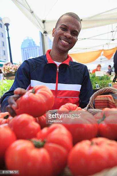Man in wheelchair with Spinal Meningitis picking up tomatoes at farmer's market