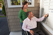 Man in wheelchair with wife getting mail from their new apartment mailbox