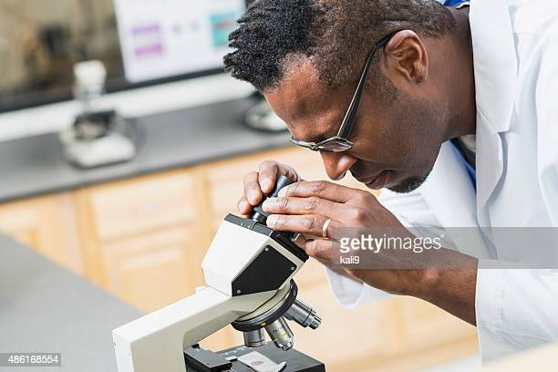 Man in white lab coat examining cells under microscope