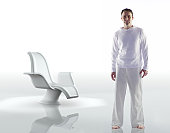 Man in white standing next to chair, portrait (Digital Composite)