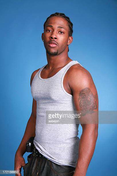 Man in white tank top with tattoo on arm in bad boy pose