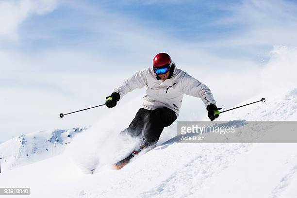 Man in white with red helmet off-piste.
