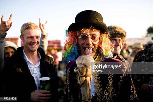Man in wig and hat with a pill on his tongue Reading Festival UK