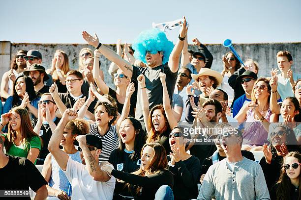 Man in wig at soccer match leading crowd cheer