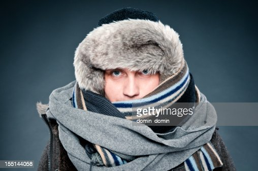 Man in winter clothes is tightly bundled up, cap, scarves