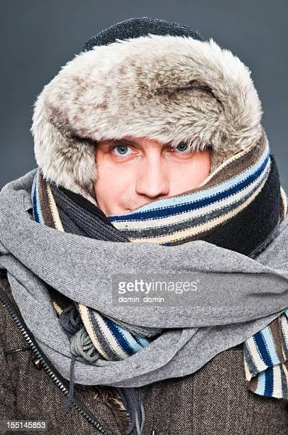 Man in winter clothes is tightly wrapped with cap, scarves