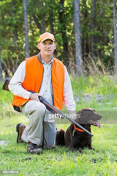 Mann im Wald mit der Schrotflinte und Hund Jagen