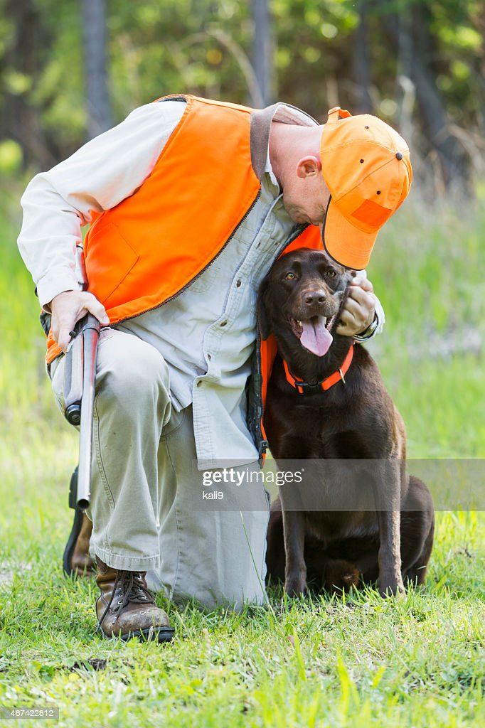 Man in woods hunting with shotgun and dog