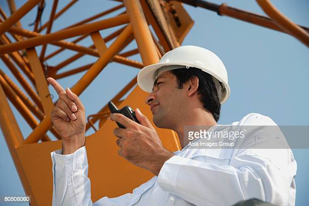 Man in work uniform pointing and using walkie talkie
