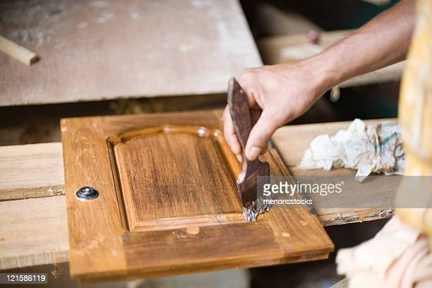 Man in workroom paints varnish on a piece of wood