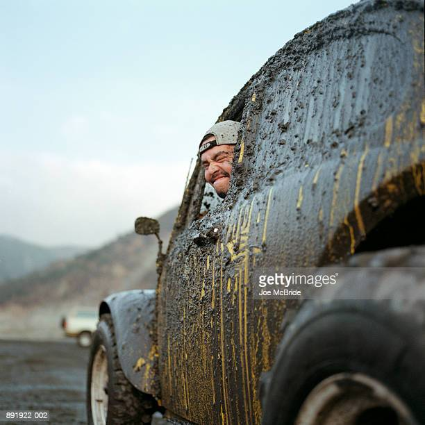 Man in yellow car covered in mud, side view
