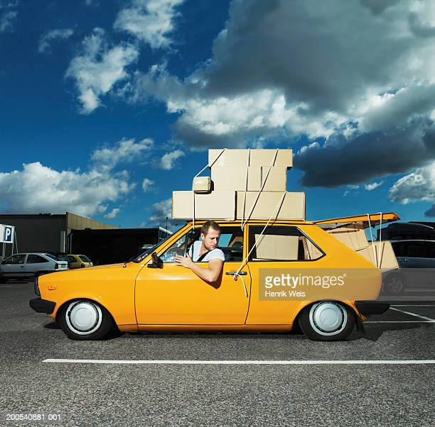Man in yellow car filled with boxes and tied to roof