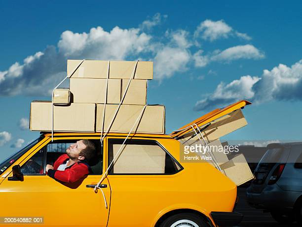 Man in yellow car filled with boxes looking up at boxes tied to roof