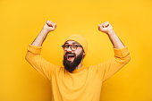 Cheerful bearded man in yellow clothes feeling happy and posing with hands up.