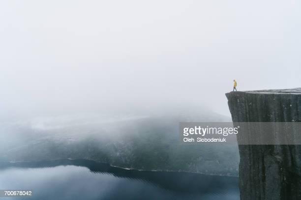 Man in yellow raincoat on the Preikestolen in fog in Norway