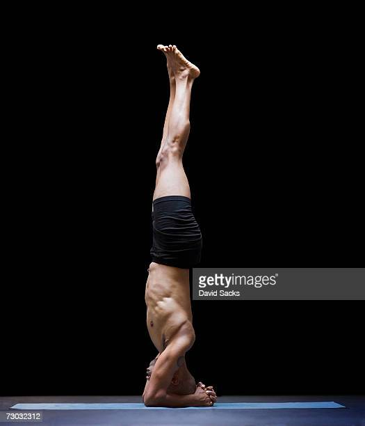 Man in yoga headstand, side view