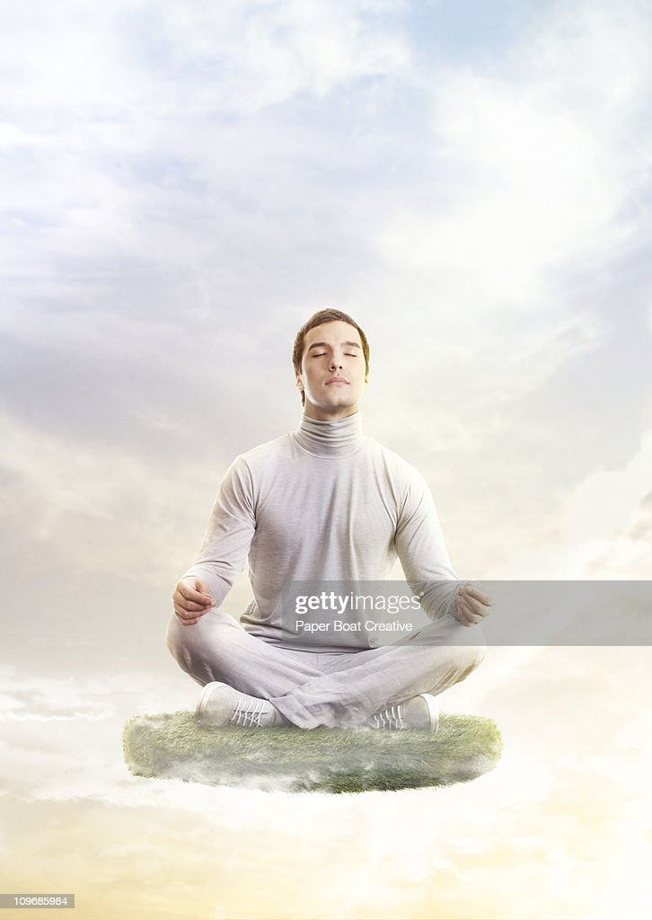 Man in yoga position, floating on a patch of grass : Stock Photo