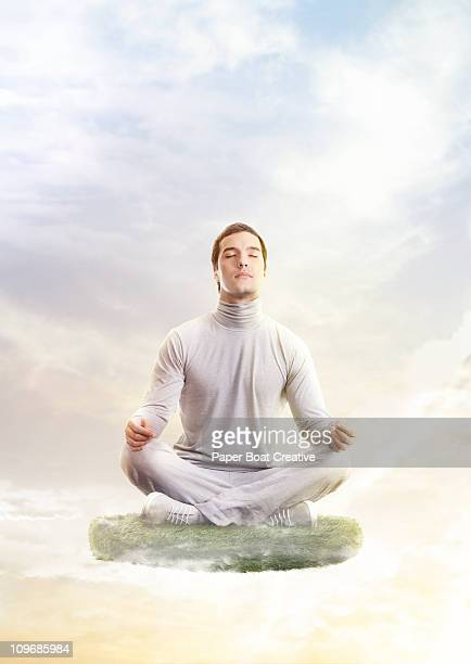 Man in yoga position, floating on a patch of grass