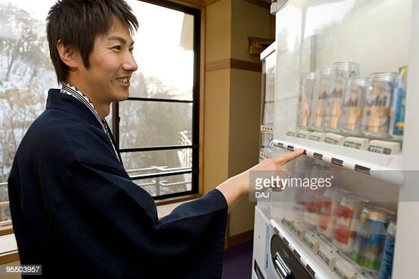 Man in Yukata using vending machine, smiling