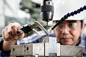 Man industrial engineer wearing hard hat work at factory.using vernier calipers.