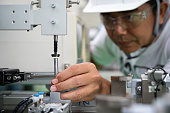 Man industrial engineer wearing hard hat work at factory.