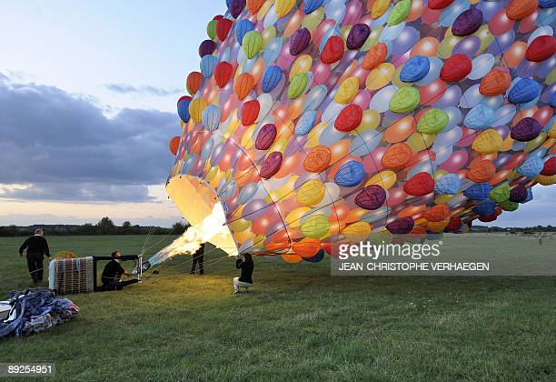 A man inflates a hotair balloon shaped like the house from the cartoon movie 'Up' on July 25 on the ChambleyBussieres aerodrome eastern France during...
