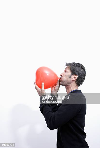 man inflating a heart balloon
