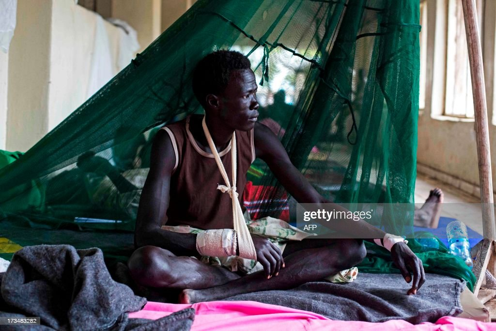 A man injured during tribal clashes that erupted in Jonglei State, sits in a hospital in Bor, South Sudan on July 15. On July 12, 2013 over 126 people were taken by air to Bor Hospital. Among them 84 were wounded by gun shots. The clashes took place in Tangnyang, in Pibor county between the rival tribes of the Lou Nuer against the Murle. AFP PHOTO/Camille Lepage