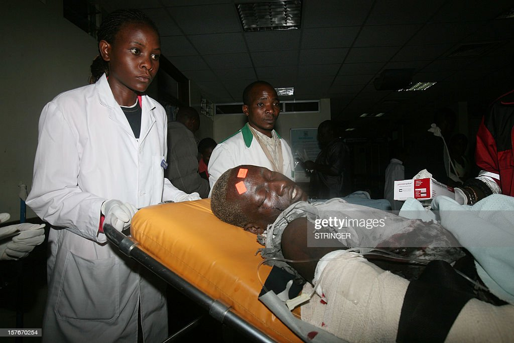 A man injured in a bomb blast is helped by medical staff at a hospital in Nairobi, on December 5, 2012. A roadside bomb in the Kenyan capital wounded at least eight people, the latest in a string of attacks, police said today. The blast, which occurred at around 7:30pm local time (1630GMT) with the streets crowded as people returned home from work, reportedly happened near a supermarket in the largely ethnic Somali neighbourhood of Eastleigh. AFP PHOTO / STRINGER