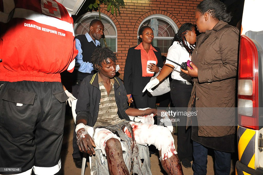 A man injured in a bomb blast is helped by rescue workers before being transported to a hospital, in Nairobi, on December 5, 2012. A roadside bomb in the Kenyan capital wounded at least eight people, the latest in a string of attacks, police said today. The blast, which occurred at around 7:30pm local time (1630GMT) with the streets crowded as people returned home from work, reportedly happened near a supermarket in the largely ethnic Somali neighbourhood of Eastleigh.