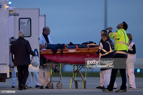 A man injured in the Nepal earthquake is stretchered to a waiting ambulance upon arrival in France early on April 30 2015 at Roissy Charles de Gaulle...