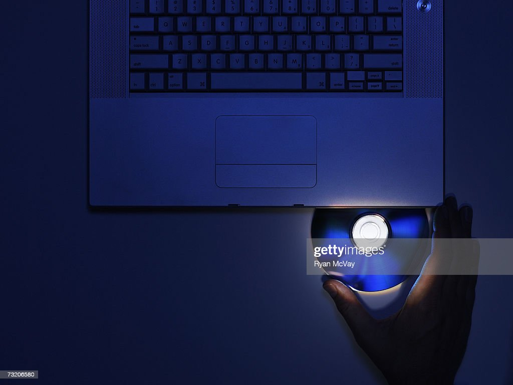 Man inserting CD disk into laptop, close up of hand, overhead view : Stock Photo