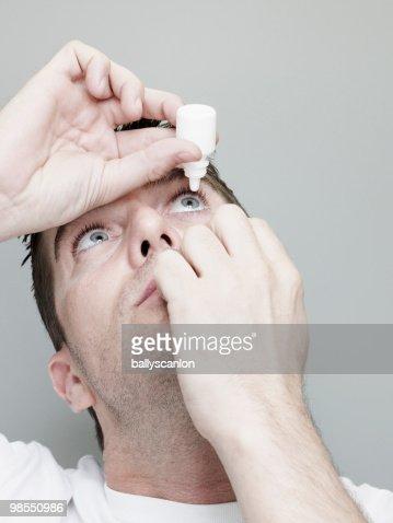Man Inserting Eye Drops Into Eye.