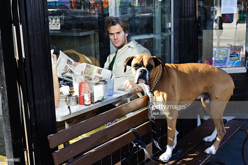 CONTENT] Man inside coffee shop and dog outside. Both do not seem happy that I was taking this photo. Humor.