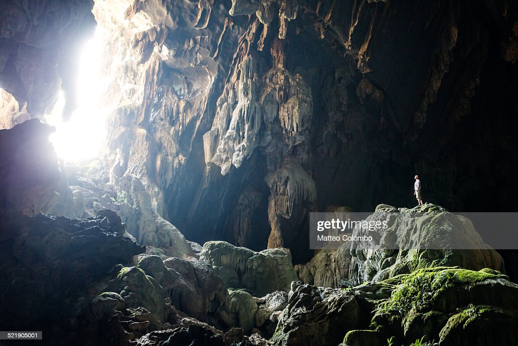 Man inside underground cave standing on a rock