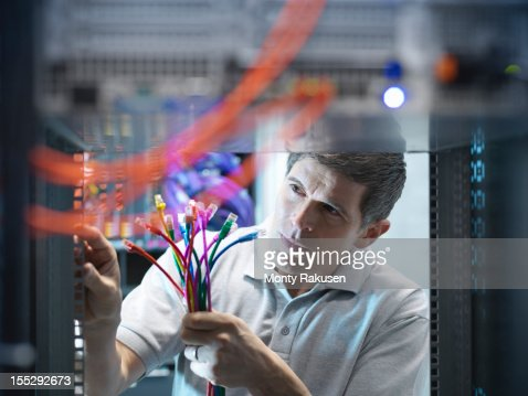 Man inspecting cables and connectors in computer server room