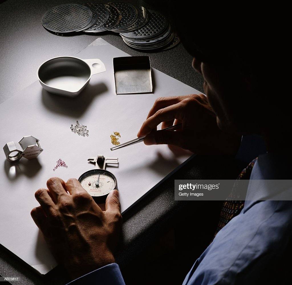 Man inspecting diamonds with tools, overhead view : Stock Photo