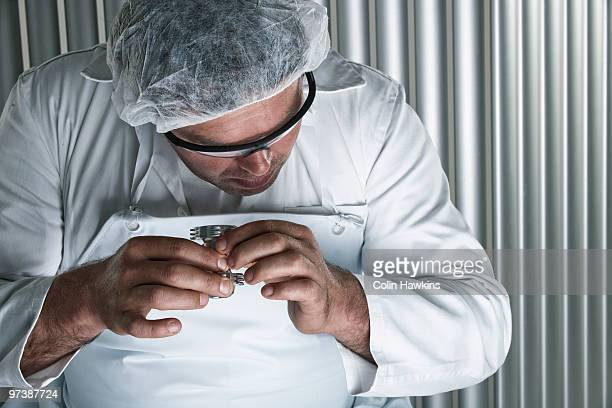man inspecting object in protective clothing