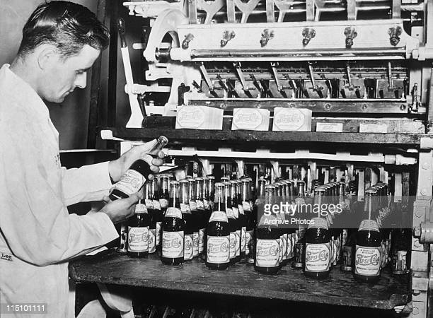 A man inspecting PepsiCola bottles coming from an automatic labelling machine in the 1940's