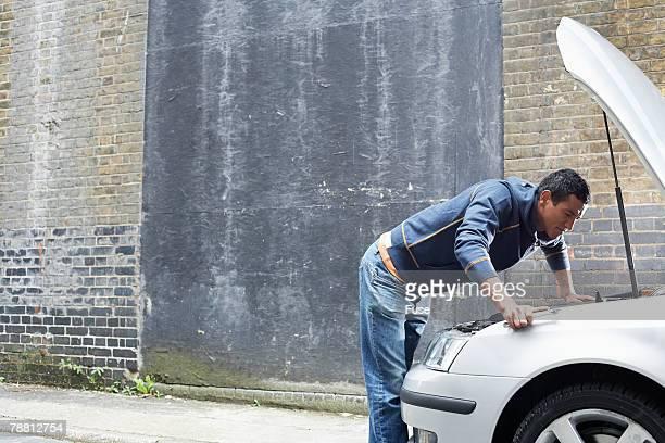 Man Inspecting Under Hood of Car