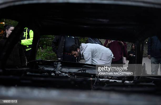 A man inspects a car gutted by fire in the Stockholm suburb of Rinkeby after youths rioted in several different suburbs around Stockholm Sweden for a...