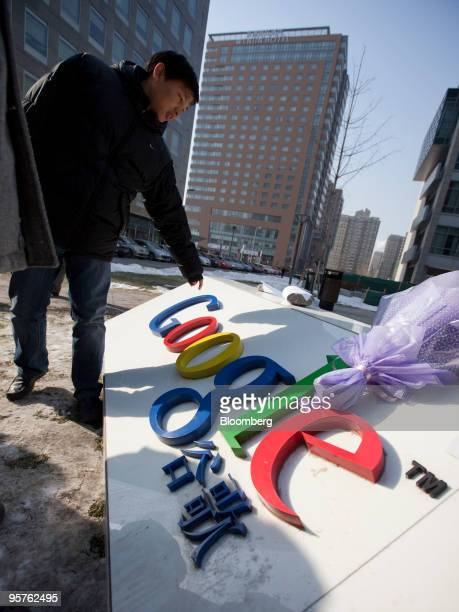 A man inspects a makeshift shrine to Google Inc outside the company's office in Beijing China on Thursday Jan 14 2010 China brushed off Google Inc's...
