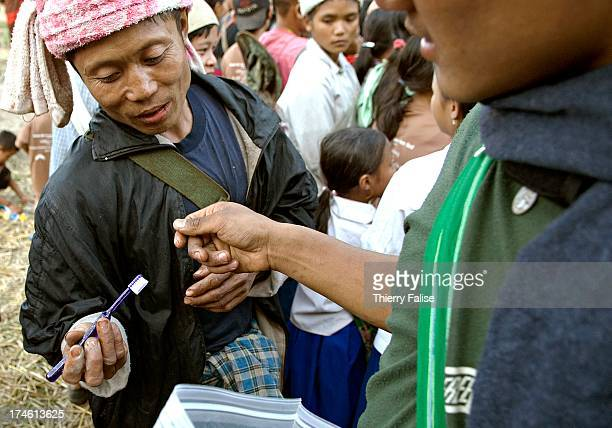 A man inspects a tooth brush he received from a Free Burma Rangers team distributing clothes toys and other items to displaced people in the jungle...