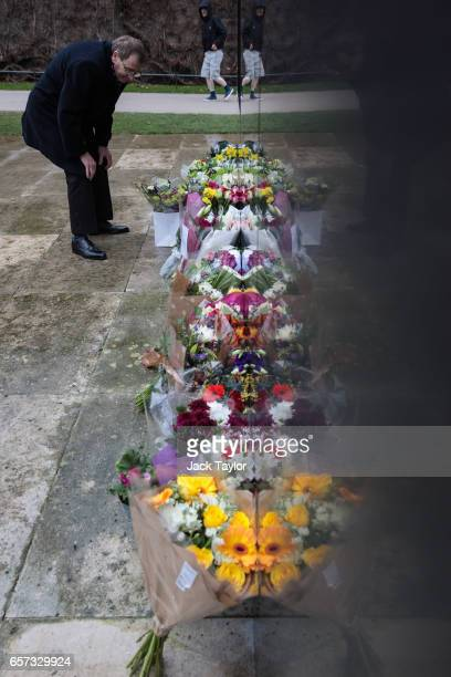A man inspects floral tributes laid in front of the National Police Memorial on March 24 2017 in London England A fourth person has died after Khalid...