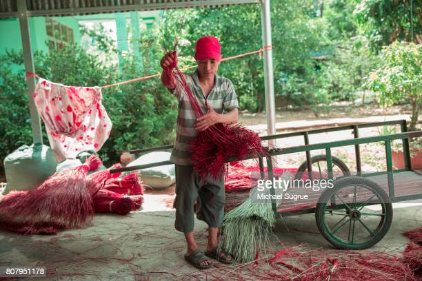 A man inspects reeds used to make a sleeping mat in the Mekong Delta, Vietnam.