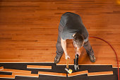 Top view of a man installing planks of hardwood floor