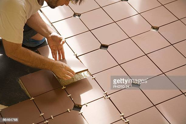 Man installing floor tile